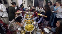 Wisatawan asing memakan hidangan iftar saat belajar tentang puasa dan budaya Uni Emirat Arab (UEA) selama Ramadan di Sheikh Mohammed Centre for Cultural Understanding (SMCCU), Dubai, UEA, Jumat (17/5/2019). (REUTERS/Satish Kumar)