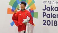 Pesilat Indonesia, Komang Harik Adi Putra menunjukkan medali emas usai memenangkan final Kelas E Putra Asian Games 2018, Jakarta, Senin (27/8). Komang menyumbang emas ke-17 Indonesia di Asian Games 2018. (Merdeka.com/Arie Basuki)