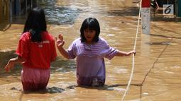 Dua anak melintasi banjir yang menggenangi kawasan Pejaten Timur, Jakarta, Jumat (26/4). Banjir yang berasal dari luapan Sungai Ciliwung tersebut merendam ratusan rumah warga hingga kedalaman lebih dari satu meter. (Liputan6.com/Immanuel Antonius)