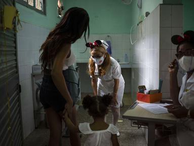 Perawat menyapa seorang anak yang tiba bersama ibunya untuk menerima dosis vaksin COVID-19 Soberana-02, di Havana, Kuba, Kamis (17/9/2021). Pemerintah Kuba memulai vaksinasi Covid-19 bagi anak-anak berusia 2 tahun dengan vaksin buatan dalam negeri. (AP Photo/Ramon Espinosa)