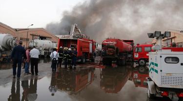 Pasukan keamanan dan pemadam berkumpul di lokasi kebakaran gudang surat suara terbesar Irak di Baghdad, Minggu (10/6). Gudang itu dilalap api sebelum dilakukan penghitungan kembali surat suara sebagaimana yang diperintahkan Parlemen. (AP/Karim Kadim)