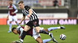 Gelandang Aston Villa, Jacob Ramsey (bawah) terjatuh saat perebutan bola dengan bek Newcastle United, Emil Krafth dalam laga lanjutan Liga Inggris 2020/2021 pekan ke-28 di St. James' Park, Jumat (12/3/2021). Aston Villa bermain imbang 1-1 dengan Newcastle United. (AP/Stu Forster/Pool)
