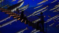 Seorang pria mengambil foto wanita berpose di galeri seni digital Infinity des Lumieres di Dubai Mall, Dubai, Uni Emirat Arab, Senin (12/7/2021). Infinity des Lumieres menggunakan proyektor digital untuk memutar gambar bergerak karya seni di galeri besar. (AP Photo/Jon Gambrell)
