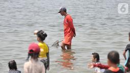 Petugas membawa jaring saat mencari ubur-ubur di Pantai Lagoon, Ancol Taman Impian, Jakarta, Rabu (9/10/2019). Kawanan ubur-ubur yang bermunculan berjenis Spotted Jellyfish, Blubber, dan Sea Netle. (merdeka.com/Iqbal Nugroho)