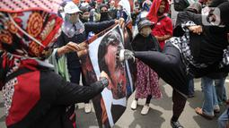 Pengunjuk rasa menendang poster bergambar Presiden Prancis Emmanuel Macron dalam aksi damai di kawasan Sarinah, Jakarta, Senin (2/11/2020). Massa demonstran dari gabungan elemen Islam mengecam pernyataan presiden Emmanuel Macron yang dianggap menghina Islam. (Liputan6.com/Faizal Fanani)