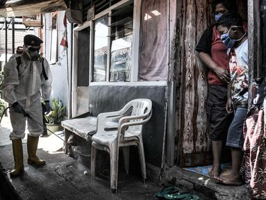 Warga menyaksikan petugas PMI Jakarta Timur  menyemprotkan disinfektan di permukiman Kampung Tengah, Kramat Jati, Minggu (23/8/2020). Penyemprotan sebagai langkah sterilisasi permukiman setelah warga di Kampung Tengah dilaporkan terpapar Covid-19. (Liputan6.com/Iqbal Nugroho)