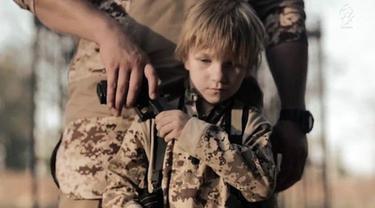 Seorang bocah berambut pirang dan berwajah bak malaikat dipaksa militan ISIS untuk menembak seorang tawanan di Irak.