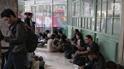 Awak media menunggu di luar kantor PSSI saat penggeledahan oleh Satgas Antimafia Bola Polri di FX Office Tower, Jakarta, Rabu (30/1). Penggeledahan terkait kasus dugaan skandal pengaturan skor pertandingan sepak bola Indonesia (Liputan6.com/Faizal Fanani)