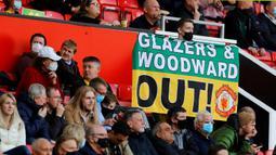 Poster berisi kecaman kepada keluarga Glazers dipasang oleh fans di area tempat duduk penonton dalam laga lanjutan Liga Inggris 2020/2021 pekan ke-37 antara Manchester United melawan Fulham di Old Trafford, Rabu (18/5/2021). Manchester United bermain imbang 1-1 dengan Fulham. (AFP/Phil Noble/Pool)