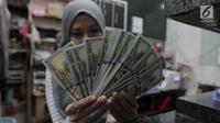 Petugas menunjukkan pecahan uang dolar Amerika di salah satu gerai penukaran mata uang asing di Jakarta, Rabu (5/9). Nilai tukar Rupiah di pasar spot menguat tipis 0,06 persen ke Rp 14.926 per dollar Amerika. (Merdeka.com/Imam Buhori)