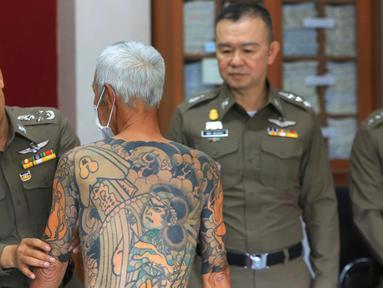 Petugas menunjukkan tato Mantan bos Yakuza asal Jepang, Shigeharu Shirai di sebuah kantor polisi saat konferensi pers di Lopburi, Thailand, Kamis, (11/1). Pria 72 tahun ini ditangkap setelah 14 tahun menjadi buronan. (AP Photo)
