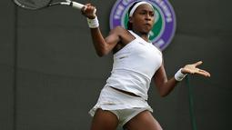 Petenis Cori Gauff berusaha mengembalikan bola pukulan Venus Williams selama pertandingan babak pertama Grand Slam Wimbledon di All England Lawn Tennis and Croquet Club, London (1/7/2019). Cori merupakan petenis AS berusia 15 tahun yang berhasil mengalahkan Venus Williams. (AP Photo/Tim Ireland)