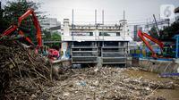 Petugas dibantu alat berat membersihkan sampah kayu dan bambu yang tersangkut di Pintu Air Manggarai, Jakarta, Rabu (9/10/2019). Sekitar 80 ton sampah sudah diangkut menggunakan alat berat. (Liputan6.com/Faizal Fanani)