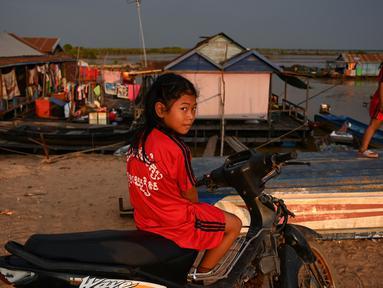 Seorang anak menaiki motor saat bermain di dekat desa terapung di sepanjang sungai Siem Reap, Kamboja (5/12/2019). Sungai Siem Reap adalah sungai yang mengalir melalui Provinsi Siem Reap, di barat laut Kamboja. (AFP/Manan Vatsyayana)