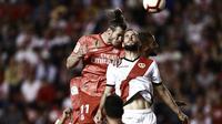 Duel penyerang Real Madrid, Gareth Bale (merah), dengan gelandang Rayo Vallecano, Mario Suarez saat kedua tim berjumpa dalam laga lanjutan La Liga di Vallecas Stadium, Puente de Vallecas, Senin dini hari WIB (29/4/2019).  (AFP/Benjamin Cremel)