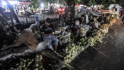 Aktivitas pedagang saat membuat bungkus atau tali ketupat di Pasar Klender, Jakarta Timur, Selasa (11/5/2021) malam. Salah satu pedagang mengaku akibat pandemi corona COVID-19 penjualan ketupat menurun hingga 70 persen. (merdeka.com/Iqbal S Nugroho)