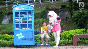 Seorang ibu menemani anaknya membaca buku yang tersedia di layanan Kotak Literasi Cerdas (Kolecer) di Taman Sempur, Bogor, Jawa Barat, Kamis (20/12). Kolecer adalah perpustakaan jalanan gratis. (Merdeka.com/Arie Basuki)