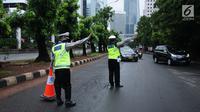 Petugas kepolisian mengarahkan kendaraan saat pengalihan arus di Jalan Jenderal Sudirman, Jakarta, Minggu (31/12). Pengalihan terkait malam puncak perayaan pergantian tahun di kawasan Bundaran HI hingga Jalan MH Thamrin. (Liputan6.com/Helmi Fithriansyah)
