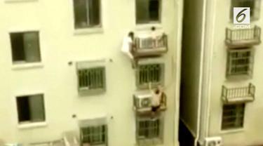 Seorang balita nyaris terjatuh dari lantai 4 sebuah gedung di China. Beruntung dua orang pria berhasil menyelamatkannya.