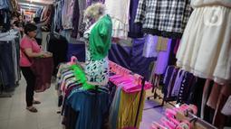 Pengunjung melintas di antara kios pedagang di Pasar Baru Metro Atom, Jakarta, Kamis (5/12/2019). PKL Senen akan direlokasi ke Pasar Baru Metro Atom lantaran para pedagang berjualan di bahu Jalan yang menyebabkan kemacetan dan terlihat kumuh. (Liputan6.com/Faizal Fanani)