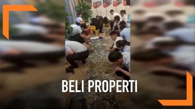 Seorang pengusaha China membayar deposit properti dengan menggunakan uang koin. Tidak tanggung-tanggung ia membawa 16 galon uang koin senilai Rp. 300 juta.