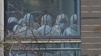 Anggota tim Organisasi Kesehatan Dunia (WHO) terlihat mengenakan APD selama kunjungan lapangan ke Pusat Pengendalian dan Pencegahan Penyakit Hewan Hubei di Wuhan di provinsi Hubei, China tengah, Selasa (2/2/2021).  Tim WHO tengah menyelidiki asal-usul virus corona. (AP Photo/ Ng Han Guan)
