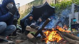 Sejumlah orang membakar kayu untuk menghangatkan diri pada hari musim dingin di Hanoi, Vietnam, Jumat (8/1/2021). Vietnam tahun ini diperkirakan mengalami musim dingin yang lebih dingin dari biasanya ketika suhu permukaan laut Samudra Pasifik turun, membentuk fenomena La Nina. (Nhac NGUYEN/AFP)