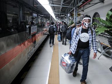 Penumpang menggunakan pelindung wajah berjalan di Stasiun Pasar Senen, Jakarta Pusat, Jumat (10/7/2020). PT. KAI membagikan face shield kepada penumpang bertujuan memudahkan masyarakat tetap dapat menjaga physical distancing di tengah pandemi COVID-19. (Liputan6.com/Faizal Fanani)