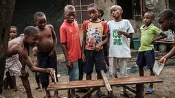 Anak-anak menggunakan potongan kayu bekas untuk bermain tenis meja di sebuah bangku di pemukiman informal Elechi Phase 3 di Port Harcourt, Nigeria selatan (14/2). (AFP Photo/Yasuyoshi Chiba)