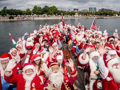 Sejumlah santa claus berlayar selama Kongres Dunia Sinterklas di Kopenhagen, Senin (23/7). Tahun ini 130 sinterklas dari berbagai penjuru dunia berkumpul di ibu kota Denmark untuk acara tiga hari tersebut. (Mads Claus Rasmussen/Scanpix via AP)