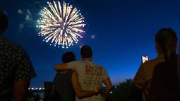 Orang-orang menyaksikan kembang api meledak di atas Pelabuhan New York di New York, Selasa (15/6/2021). New York menandai berakhirnya pembatasan COVID-19 dengan perayaan kembang api di seluruh negara bagian untuk menghormati para kelompok pekerja penting. (AP Photo/Craig Ruttle)