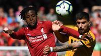 Striker Liverpool, Divock Origi, duel udara dengan gelandang Wolverhampton, Ruben Neves, pada laga Liga Inggris di Stadion Anfield, Liverpool, Minggu (12/5). Liverpool menang 2-0 atas Wolves. (AFP/Paul Ellis)