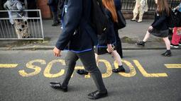 Aktivitas pelajar Holyrood Secondary School saat berangkat ke sekolah untuk pertama kalinya di Glasgow, Skotlandia (12/8/2020).  (AFP/ANDY BUCHANAN)