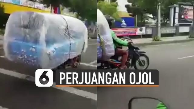 Beredar video memperlihatkan pengemudi ojek online memgangkut kasur dengan motor.