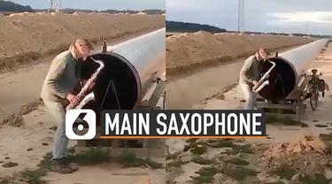 Aksi unik pria ini bermain saxophone di dekat pipa besar. Suaranya membuat musik jadi asik.