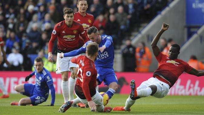 Bek Manchester United, Luke Shaw, menghadang pemain Leicester City, James Maddison, pada laga Premier League di Stadion King Power, Minggu (3/2). Manchester United menang 1-0 atas Leicester City. (AP/Rui Vieira)