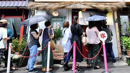 Pelanggan mengantre untuk membeli kakigori atau es serut yang menggunakan es alami di distrik Yanaka Tokyo (21/6/2019). Dilansir Japan Experience, Kakigori telah ada sejak periode Heian atau sekitar abad ke-11. (AFP Photo/Toshifumi Kitamura)