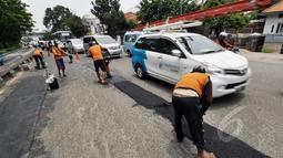 Petugas mengaspal jalanan yang berlubang di Jalan Kramat Raya, Jakarta, Rabu (25/2/2015). Perbaikan dilakukan karena jalan bergelombang dan berlubang setelah terendam banjir beberapa waktu lalu. (Liputan6.com/Faizal Fanani)