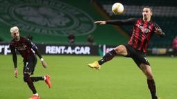 Penyerang AC Milan, Zlatan Ibrahimovic, berusaha mengontrol bola saat menghadapi Celtic pada laga Grup H Liga Europa 2020/2021 di Celtic Park Stadion, Jumat (23/10/2020). AC Milan menang 3-1 atas Celtic. (AFP/Russell Cheyne/pool)