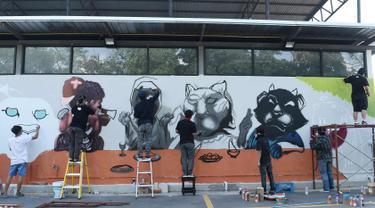 Sejumlah seniman grafiti membuat mural harimau kumbang di Bangkok, Thailand (16/3). Aksi ini sebagai protes perburuan liar ilegal oleh konglomerat konstruksi Premchai Karnasuta. (AFP Photo/Lillian Suwanrumpha)
