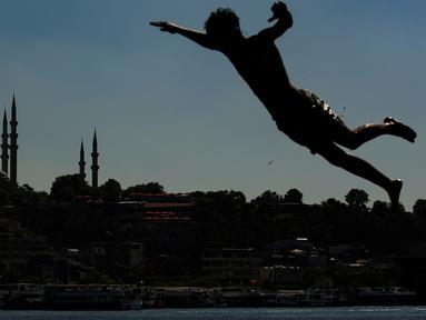 Berlatar belakang Masjid Suleymaniye yang bersejarah, seorang pemuda melompat ke Tanduk Emas (golden horn) mengarah ke Selat Bosphorus yang memisahkan Eropa dan Asia, di Istanbul, Turki pada 3 Juli 2020. (AP Photo/Emrah Gurel)