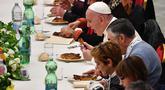 Paus Fransiskus (kanan) menyantap makan siang bersama sejumlah orang miskin di Pope Paul VI hall, Vatikan, Minggu (18/11). Makan siang bersama ratusan kaum papa, tunawisma, dan pengangguran itu memperingati Hari Orang Miskin Sedunia. (Vincenzo PINTO/AFP)