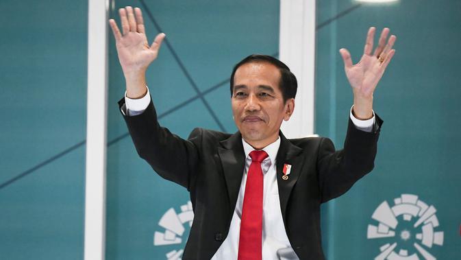 Presiden Republik Indonesia, Joko Widodo, menyapa penonton saat pembukaan Asian Games 2018, Sabtu (18/8/2018). (AFP/Jewel Samad)