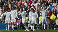 Pemain Real Madrid melakukan selebrasi usai striker mereka Cristiano Ronaldo membobol gawang Atletico Madrid dalam pertandingan La Liga Spanyol di stadion Santiago Bernabeu di Madrid (8/4). (AP Photo / Francisco Seco)