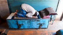 Umat Muslim melaksanakan salat di depan toko-toko yang tutup di sebuah pasar selama bulan Ramadan saat penerapan lockdown di New Delhi, Senin (4/5/2020). Di emperan toko-toko yang tutup, umat muslim salat berjemaah dengan menjaga jarak dan lainnya membaca kitab suci Alquran. (Sajjad HUSSAIN/AFP)