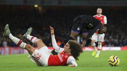 Gelandang Arsenal, Matteo Guendouzi, terjatuh saat berebut bola dengan pemain Crystal Palace, Wilfried Zaha, pada laga Premier League 2019 di Stadion Emirates, Minggu 927/10). Kedua tim bermain imbang 2-2. (AP/Leila Coker)