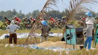 Petani berhenti menjemur gabah untuk menonton balapan Tour de Singkarak 2016 pada Etape 6 dari Padang Pariaman menuju Sawahlunto, Sumatera Barat, Kamis (11/8/2016). (Bola.com/Nicklas Hanoatubun)