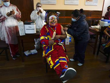 "Seorang badut disuntik vaksin COVID-19 Sinopharm selama kampanye vaksinasi yang menargetkan usia antara 18 dan 30 tahun di Universitas Negeri San Andres di La Paz, Bolivia, Senin (5/7/2021). Presiden Luis Arce menjanjikan upaya vaksinasi ""besar-besaran"" pada Juli dan Agustus. (AP Photo/Juan Karita)"