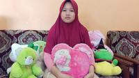 Azahra Zenita Putri, adik keempat dari Indah Halimah Putri, penumpang Sriwijaya Air SJ-182 yang mengalami kecelakaan pada Sabtu (9/1/2021) lalu, berfoto bersama boneka pemberian kakak perempuannya (Liputan6.com / Nefri Inge)