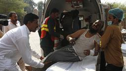 Petugas rumah sakit memindahkan seorang pria yang terluka dalam kebakaran kereta api, ke sebuah rumah sakit di Multan, Pakistan  (31/10/2019). Sekitar 70 orang dilaporkan tewas dengan puluhan lainnya terluka akibat terbakarnya kereta api tersebut. (AP Photo/Asim Tanveer)